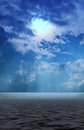 Clouds with sun beams signing through onto sea Royalty Free Stock Photo