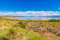 Cloudscape over blue lake scenic view of or sea with green countryside foreground Royalty Free Stock Image