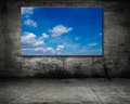 Cloudscape on screen over a gray wall Royalty Free Stock Photo