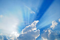 Cloudscape with sunrays bursting through clouds in a blue sky Stock Images