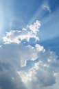 Cloudscape with sunrays bursting through clouds in a blue sky Royalty Free Stock Photo
