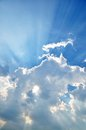 Cloudscape with sunrays bursting through clouds in a blue sky Stock Photography