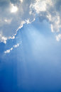 Cloudscape with sunrays bursting through clouds in a blue sky Royalty Free Stock Images
