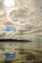 Cloudy beach mirror image of shore Stock Photography
