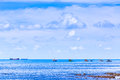 Cloudy blue sky above a fishing boat in the sea Stock Photo