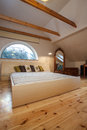 Cloudy home huge bright bed wooden bedroom interior Royalty Free Stock Photo