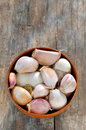 Cloves and bulbs of garlic in a wooden bowl isolated on old background Stock Photography
