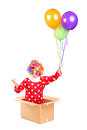 A clown in a cardboard box holding balloons isolated against white background Royalty Free Stock Photo