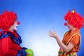 Clown couple playing with ballon on blue background Royalty Free Stock Photo