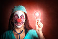 Clown doctor holding red emergency lightbulb portrait of a smiling light bulb Stock Photo