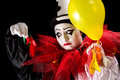 Clown with exploded balloons sad pierrot holding the left overs of his Royalty Free Stock Photo