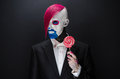 Clown and halloween theme scary clown with pink hair in a black jacket with candy in hand on a dark background in the studio Stock Photo