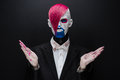 Clown and Halloween theme: Scary clown with pink hair in a black jacket with candy in hand on a dark background in the studio Royalty Free Stock Photo