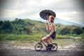 Clown riding a little bike with an umbrella beautiful woman holding and Stock Image