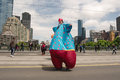Clown on stilts on parade smiling in bright cloth walking emirates melbourne cup with clouds and skyscrapers in background Royalty Free Stock Images