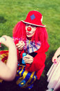 Clown woman blowing soap bubbles in vintage style outdoor birthday celebration Stock Images