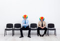Clowns waiting businessmen wearing clown wigs sitting on row of chairs Royalty Free Stock Images