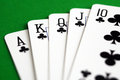 Clubs royal flush poker playing cards over green table Stock Photography