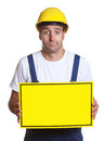 Clueless latin construction worker with sign Royalty Free Stock Photo