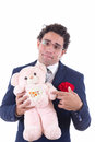 Clumsy man holding a teddy bear with glasses Stock Image