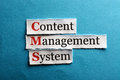Cms abbreviation content management system on blue paper Royalty Free Stock Photos