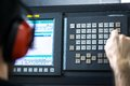Cnc operator at metal machining milling center in tool workshop inserting data with keyboard wearing mechanical technician worker Royalty Free Stock Photo