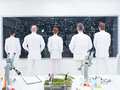 Co workers laboratory analysis general view of five scientists in a chemistry lab in front of a blackboard analyzing formulas on a Royalty Free Stock Images
