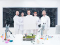 Co workers in laboratory close up of five scientists a chemistry lab holding hands an empty banner and confident looking the Royalty Free Stock Photos