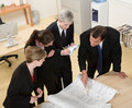 Co-workers reviewing blueprints Royalty Free Stock Photos