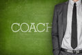 Coach on blackboard with businessman in a suit side Royalty Free Stock Image