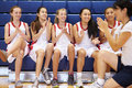 Coach of female high school basketball team gives team talk whilst sitting on bench clapping Stock Photos