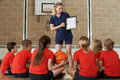 Coach giving team talk to elementary school basketball team gives Royalty Free Stock Image