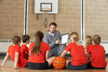 Coach giving team talk to elementary school basketball team gives Royalty Free Stock Images