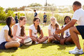 Coach giving team talk to female high school soccer team outside kneeling down Royalty Free Stock Photo