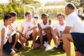 Coach giving team talk to male high school soccer team outside with people in background Royalty Free Stock Photo
