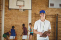 Coach smiling at camera while high school team playing basketball in background Royalty Free Stock Photo
