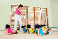 Coach teaching little girls group of children engaged in physical training in gym Royalty Free Stock Photography