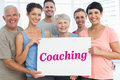 Coaching against grey wall the word and fit people holding blank board in yoga class Stock Photos