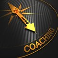 Coaching business background golden compass needle on a black field pointing to the word d render Royalty Free Stock Images