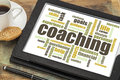 Coaching word cloud concept a related on a digital tablet with cup of coffee Royalty Free Stock Photography