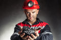 Coal miner holding lump of coal against a dark background Stock Images