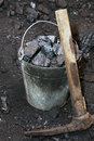 Coal mining. Pickaxe and the bucket with coal in mine Royalty Free Stock Photo