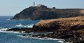 Coast of arinaga gran canaria canary islands in low tide with lighthouse in background aguimes Royalty Free Stock Image