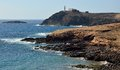 Coast of arinaga gran canaria canary islands in low tide with lighthouse in background aguimes Royalty Free Stock Images