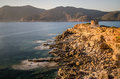 Coastal cliff with ruins of watch tower sardinia long exposure picture illuminated by sunset italy Stock Photography