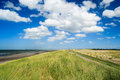 Coastal landscape under a sunny blue sky with fluffy white clouds sea beach dunes and road is visible the picture has summer Royalty Free Stock Image