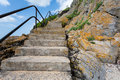 Coastal steps leading upwards with a metal safety rail Royalty Free Stock Images