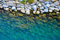Coastal stones trough clear blue water in natural light Royalty Free Stock Image