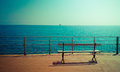 Coastline beautiful tranquil scene with bench, vintage Royalty Free Stock Photo