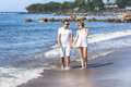 Coastline loving couple walking along the Royalty Free Stock Photos